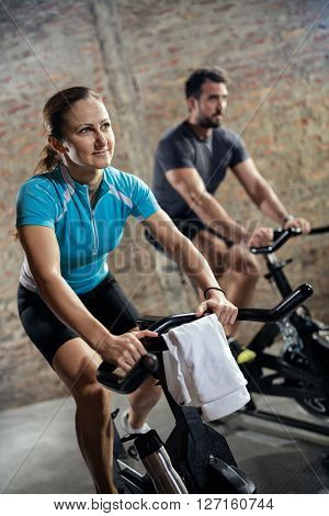 Sporty fit couple in sports clothing doing training on bicycle