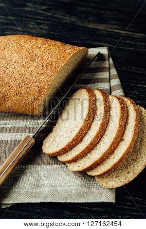 Sliced bread and knife on linen cloth on black wooden table