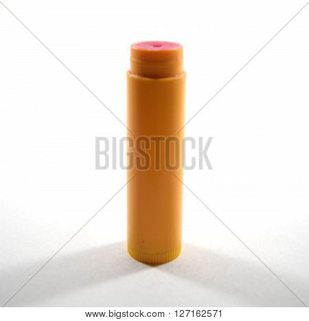 Red flavored chapstick (not branded) with cap off - isolated