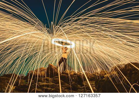 Burning steel wool spined on stone. Long exposed to light and spark lines