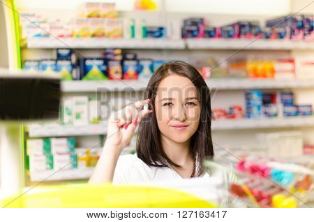 Pharmacist chemist woman show a pill. Pharmacy drugstore is background. Pretty, young woman. Pharmaceutical.