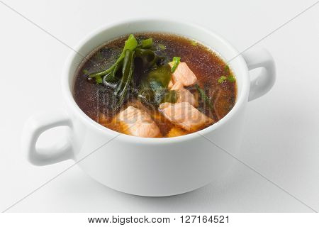miso soup with salmon, wakame seaweed, fish broth, soy sauce and leek in white tureen on white background