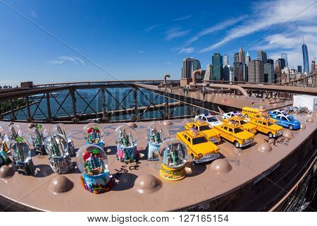 NEW YORK - AUGUST 22, 2015: Toys on the Brooklyn Bridge with view to Downtown skyline of New York on August 22, 2015. Its a famous and iconic bridge in New York which passes the east river.