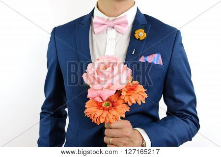 Man in blue suit with pink bow tie flower brooch and pink blue strip pocket square close up carry flowers