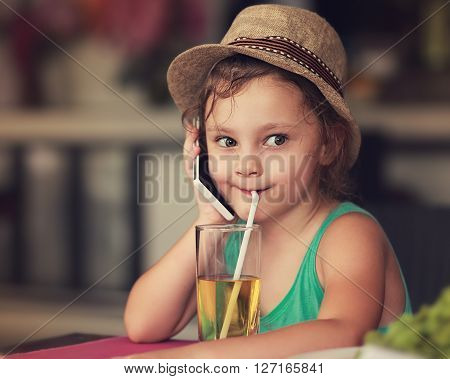Fun happy kid girl talking on mobile phone and drinking apple juice in cafe. Toned closeup portrait