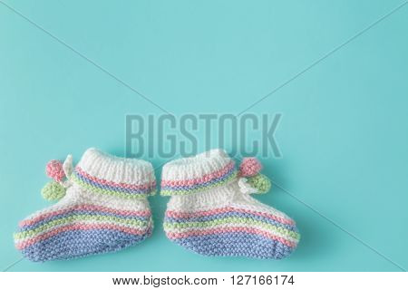 Newborn Announcement Template. Handmade Knitted Booties On Plain Background
