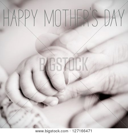 text happy mothers day in a closeup of the hand of a baby gripping the finger of his or her mom, in black and white