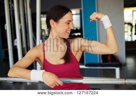 Smiling woman looks at her biceps in sport club and holding on to the rod in sport club
