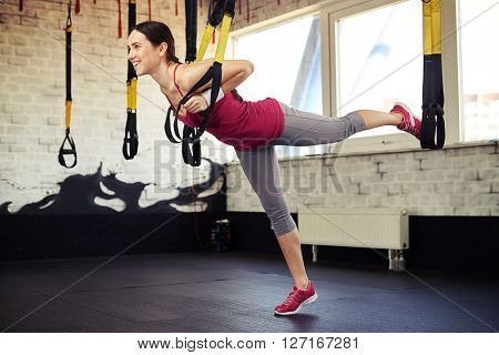 Smiling woman standing stretched using trx in sport club