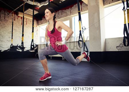 Young smiling girl in sportswear is squats using a trx