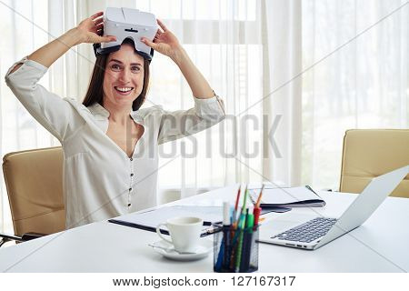 Young woman is smiling wearing virtual reality glasses on the top of her head
