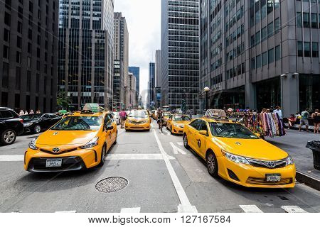 NEW YORK - AUGUST 23, 2015: View to New Yorks taxicabs at the 5th Av on August 23, 2015. The taxicabs of New York City are widely recognized icons of the city come in two varieties: yellow and green.