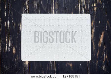 complete white puzzle on dark wooden desk