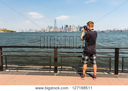 ?NEW YORK AUGUST 24: A man taking photos from the Manhattan skyline New York August 24 2015. This view is from the Liberty Island where the Statue of Liberty stands.