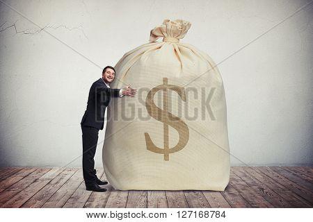 Happy man hugging a big bag of money, grey wall on background