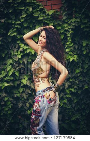 young happy woman in boho style clothes blue embroidered and golden top in garden summer day