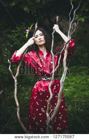 young woman in red kimono stand in garden holding big branch