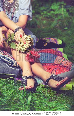 summer boho style fashion woman sit in garden holding silk flowers in hands closeup