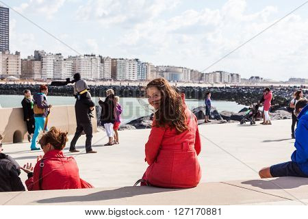 OOSTENDE, BELGIUM - AUGUST 21, 2014: A girl in a red coat in Oostende, Belgium on August 21, 2014. Oostende is a town in east Belgium at the Atlantic sea.
