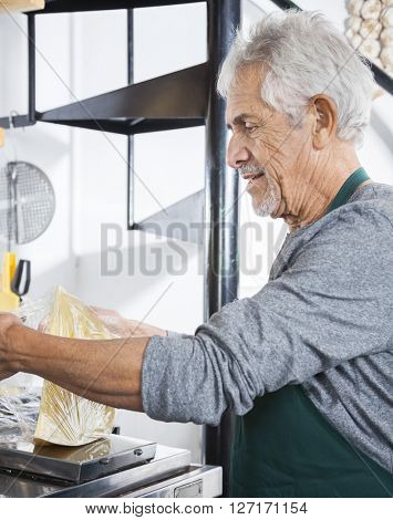 Senior Salesman Packing Cheese At Grocery Store