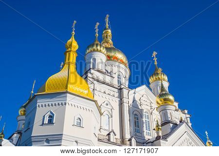 Pochayiv Lavra - church golden domes against the clear blue sky. Ukraine