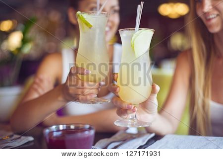 Two beautiful women having fun in a bar drinking cocktails