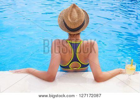 Pretty brunette woman in a hat enjoying lemonade in a swimming pool