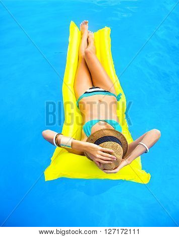 Young pretty woman with perfect tanned body lying on yellow air mattress in the pool