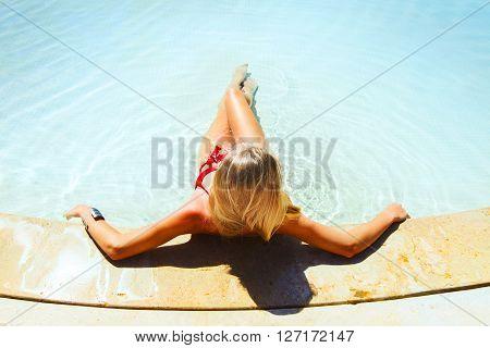 Pretty blond woman enjoying a swimming pool
