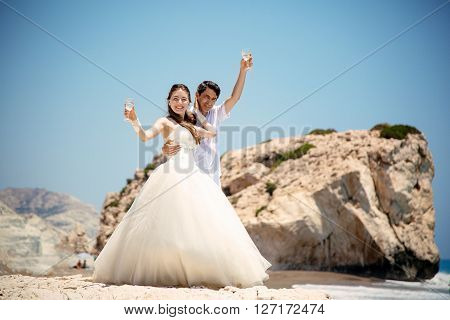 the bride and groom with glasses of champagne on the background of a sea, wedding ceremony  on cyprus ** Note: Visible grain at 100%, best at smaller sizes
