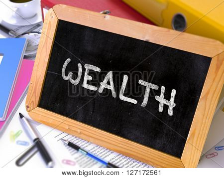 Wealth Handwritten on a Blackboard. Composition with Small Chalkboard on Background of Working Table with Office Folders, Stationery, Reports. Blurred Background. Toned Image. 3D Render.