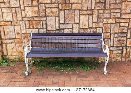 Park Bench Against Concrete Patterned Background Wall