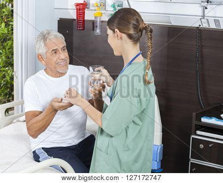 Happy Patient Receiving Medicine And Water Glass From Nurse