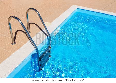 water in blue swimming pool with steps in summer season