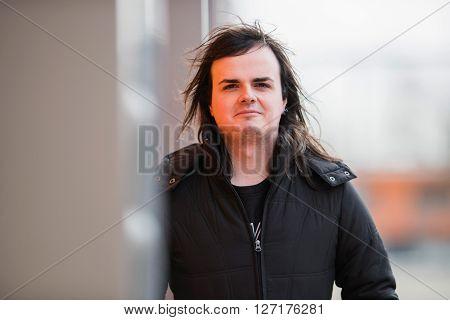 Feminine Man Leaning Against Industrial Metal Wall
