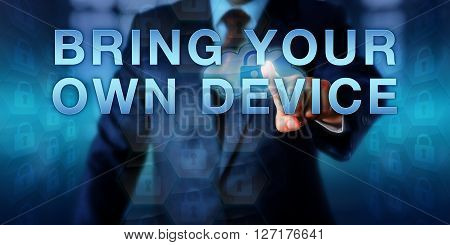 Business manager is pressing BRING YOUR OWN DEVICE. Short BYOD. Information technology concept working on your personal computing device to access privileged corporate information of your employer.