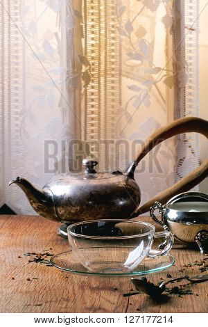Glass Cup Of Hot Tea With Dry Green Tea Leaves, Vintage Spoon And Sugar. Rustic Wooden Backgtound.