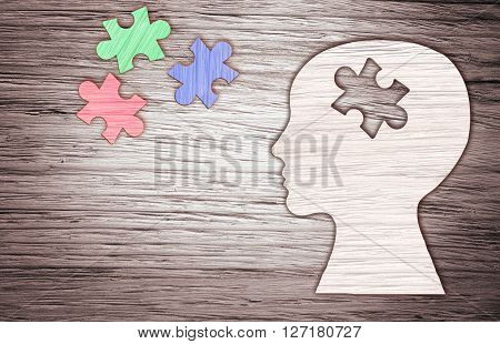 Human head silhouette with a jigsaw piece cut out on the wooden background mental health symbol