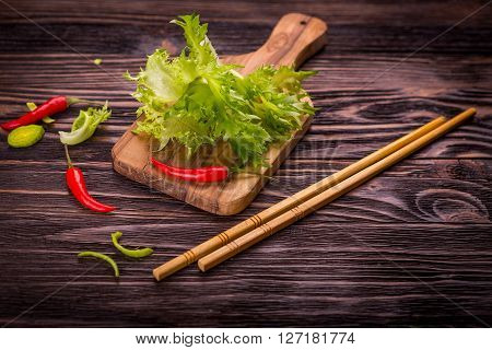 Ingredients of Asian cuisine - rice noodles leek lettuce red hot pepper on a dark wooden background