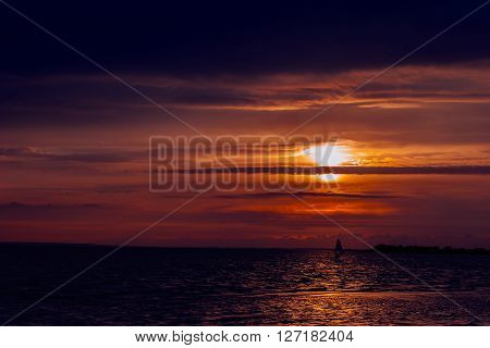 windsurfer silhouette against a sunset background at the sea