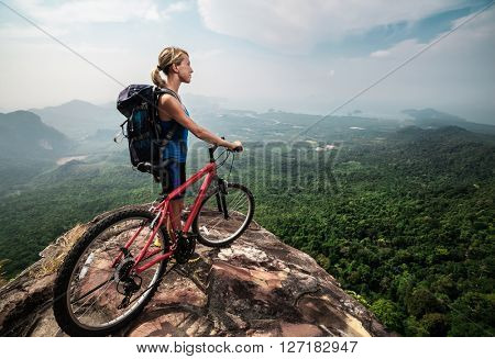 Young lady with Bicycle standing on mountain