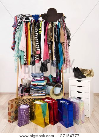 Wardrobe with clothes and shopping bags. A lot of clothes and accessories hanging on a rack nicely arranged on hangers and in piles.