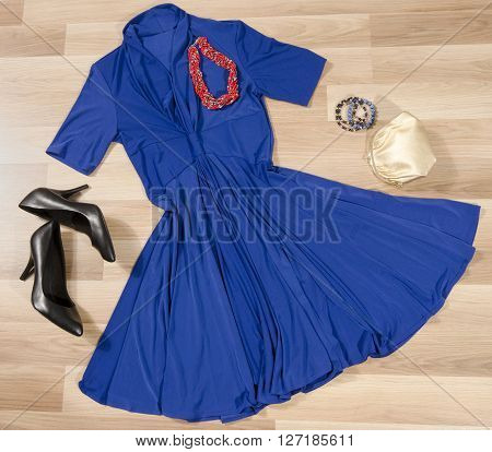 Dark blue dress and accessories arranged on the floor. Woman dress with accessories purse high heel shoes and necklace.