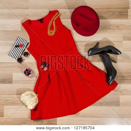 Red dress and accessories arranged on the floor. Woman pleated dress with accessories purse hat high heel shoes and vintage sunglasses.