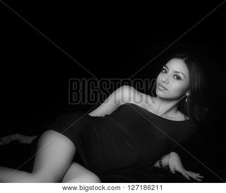 Beautiful exotic young woman lounging in black dress
