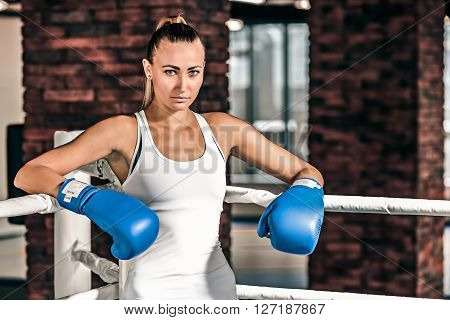 Young pretty boxer woman standing on ring and resting. Beautiful fair-haired girl wearing blue boxing gloves. Resting during or after the boxing workout.