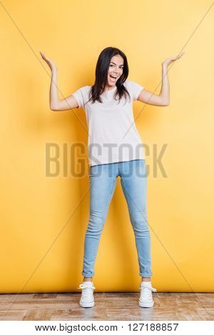 Full length portrait of a cheerful woman shrugging shoulders on yellow background