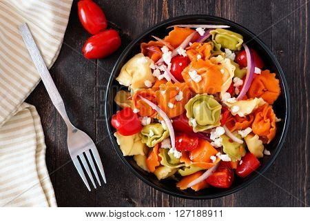 Bowl Of Colorful Tortellini Pasta Salad With Tomatoes And Onions, Overhead Scene On Dark Wood Table