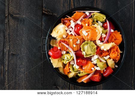 Bowl Of Multicolored Tortellini Pasta Salad With Tomatoes And Onions, Overhead View On A Dark Wood B