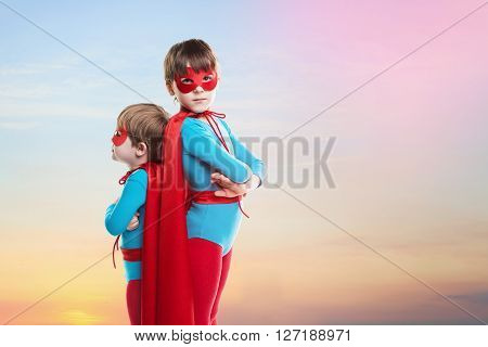 Children boys play superheroes. Children on sunset sky background. Power concept.